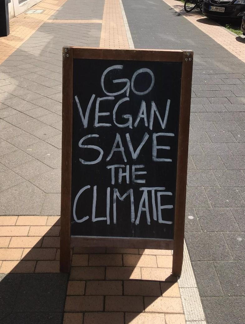 Schild mit der Aufschrift: Go vegan, save the climate