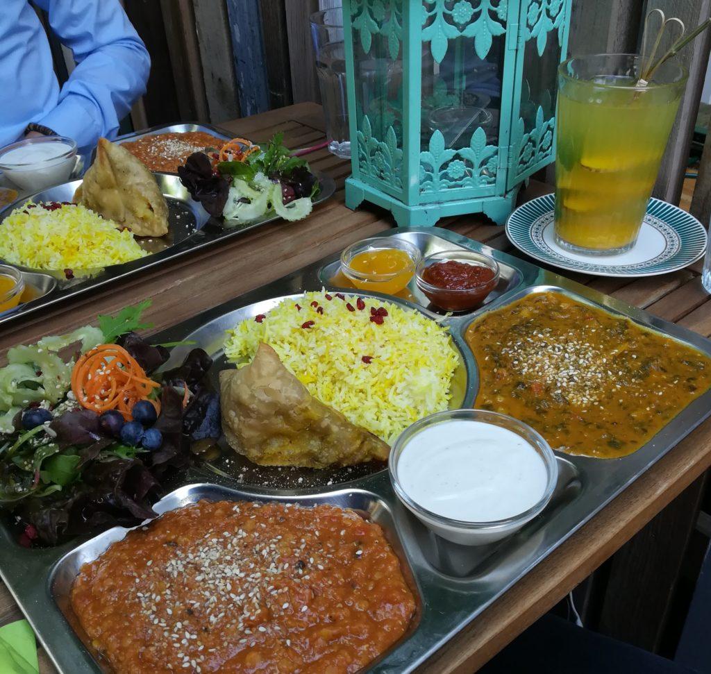 Eine große Platte (Thali) mit Curry, Dhal und Samosas