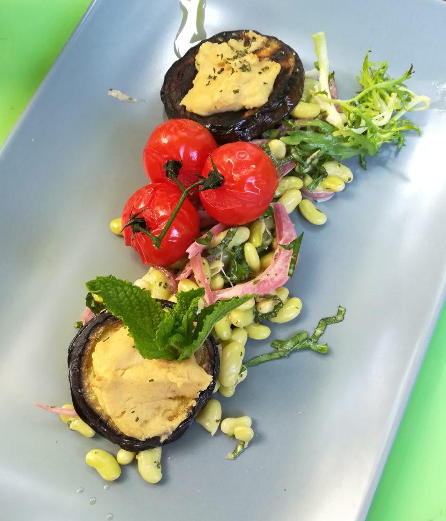 Mit Bluffmozarella überbackene Aubergine dazu Saubohnen-Minz-Salat und geschmolzene Tomate